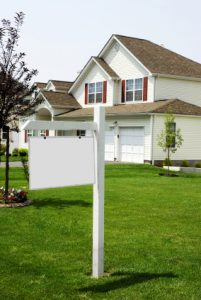 white house with for sale sign out front